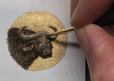 Rachelle Siegrist working on a miniature painting of a cape buffalo